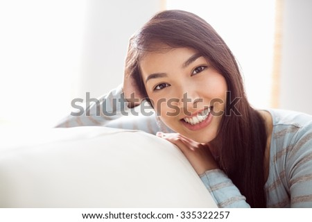 Asian woman relaxing on couch at home in the living room #335322257