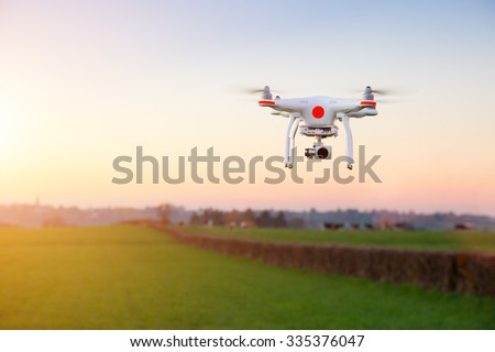 Modern RC Drone / Quadcopter with camera flying on a clear sunny sky sunset background with nice lens flare. #335376047