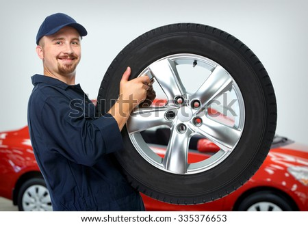 Smiling car mechanic with a tire over red car background. #335376653