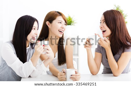 three happy young woman chatting in living room #335469251