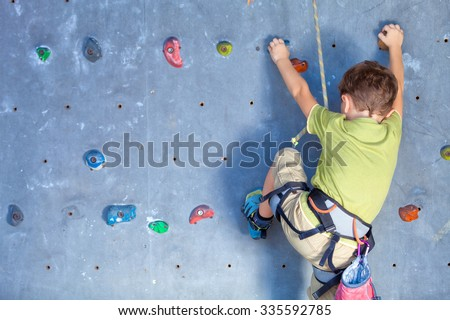 little boy climbing a rock wall indoor Royalty-Free Stock Photo #335592785