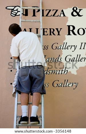 A sign painter on a ladder repairing a damaged sign