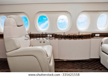 Aircraft business class interior with blue sky outside the portholes #335621558