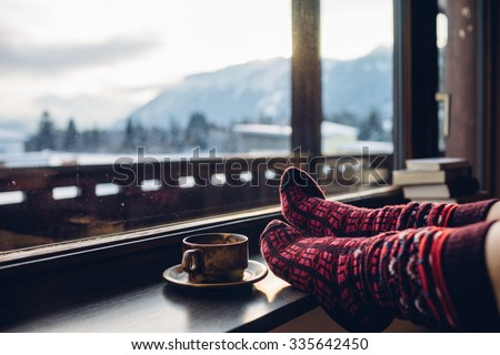 Feet in woollen socks by the Alps mountains view. Woman relaxes by mountain view with a cup of hot drink. Close up on feet. Winter and Christmas holidays concept. #335642450