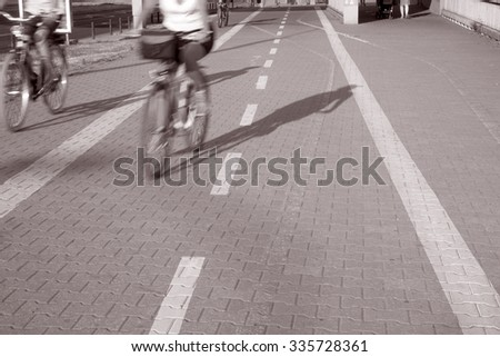 Bike Lane with Cyclist in Urban Setting in Black and White Sepia Tone #335728361