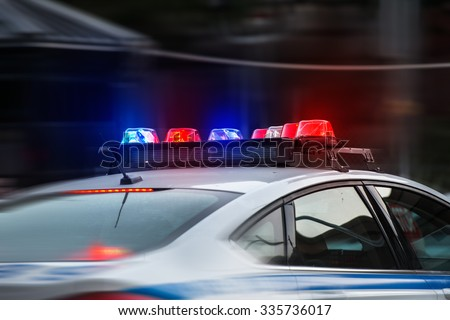 A police car rushes to the emergency call with lights turned on