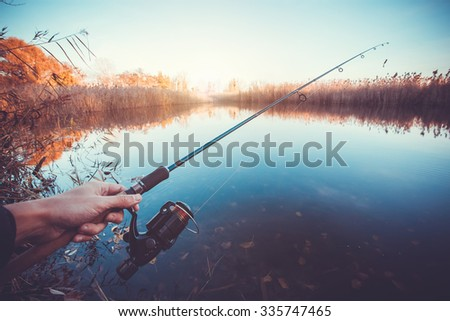 hand with spinning and reel on the summer lake #335747465