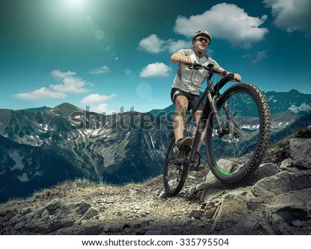Man in helmet and glasses stay on the bicycle under sky with clouds. #335795504