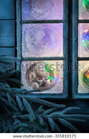Adorable teddy bear for Christmas in frozen window #335810171