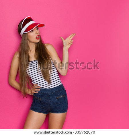 Shooting Sexy Girl. Young woman in striped shirt and red sun visor showing finger gun. Three quarter length studio shot on pink background. #335962070