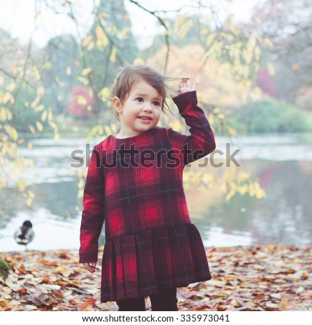 Toddler girl in red tartan dress playing with falling leaves and sticks standing in front of the lake holding her hair, selective focus. Photo with applied vintage effect filters