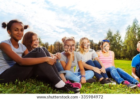 Smiling international friends sitting on grass #335984972