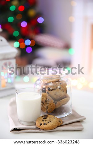 Christmas cookies and glass of milk on table at home  #336023246
