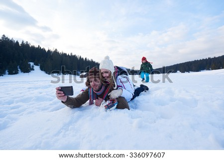 happy  romantic couple have fun in fresh snow and taking selfie. Romantic winter scene in forest with young people