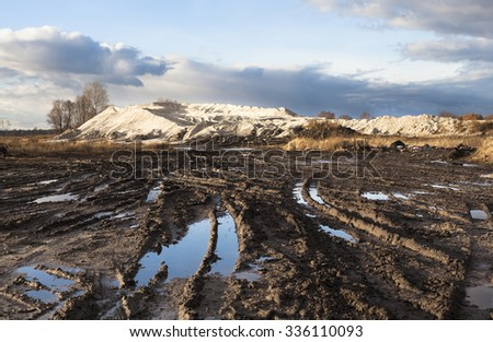 Mud and puddles on the dirt road with sand hills in the background. #336110093