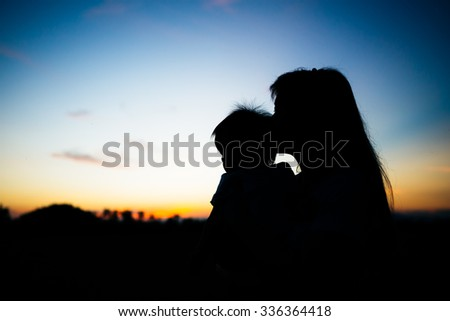 a silhouette picture of mother kissing her baby while the sunset and twilight sky. #336364418