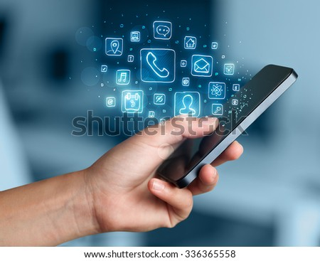 Hand holding smartphone with glowing mobile app icons #336365558