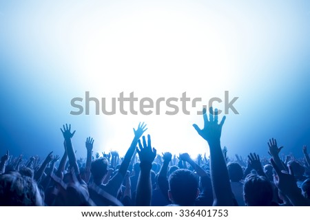 silhouettes of concert crowd in front of bright stage lights Royalty-Free Stock Photo #336401753