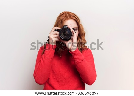 studio shot of redhead woman with dslr camera, photographer on white background
