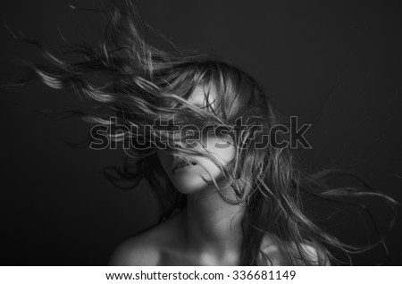Dramatic portrait of a girl theme: portrait of a beautiful girl with flying hair in the wind against a background, black and white photography
