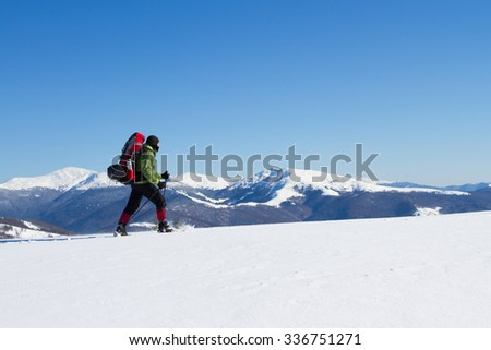 Winter hiking in the mountains on snowshoes with a backpack and tent. #336751271