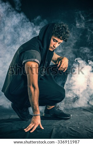 Handsome tough young man in dark hooded t-shirt on dark background, looking away #336911987