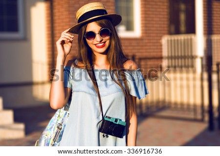 Young pretty hipster cheerful girl posing on the street at sunny day, having fun alone, stylish vintage clothes hat and sunglasses, travel concept , young photographer with vintage camera. #336916736