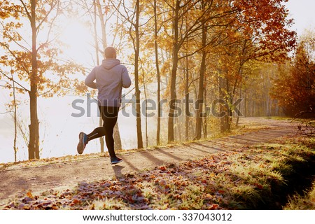 Man running in park at autumn morning. Healthy lifestyle concept Royalty-Free Stock Photo #337043012
