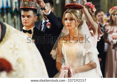 Religious blonde bride and handsome groom in crowns in church at the wedding ceremony #337192157