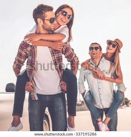 Friends having fun. Two beautiful young couples having fun near their white convertible #337195286