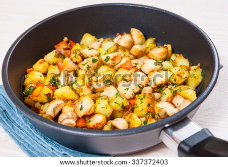 Fried potato with mushrooms in a frying pan #337372403