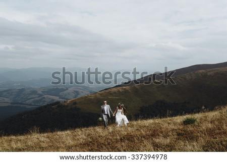 beautiful stylish groom holding fabulous happy emotional bride   on the background of the sunny stunning mountains #337394978