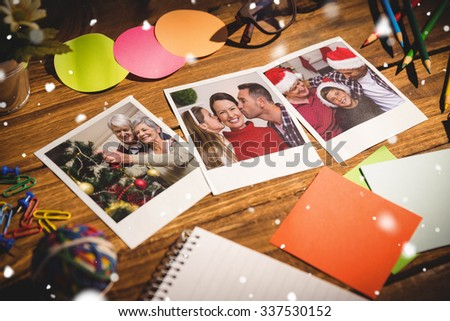 Snow falling against high angle view of office supplies with blank instant photos #337530152