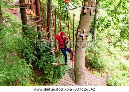 Girl seen from above climbing in high rope course #337626542