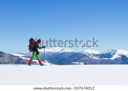 Winter hiking in the mountains on snowshoes with a backpack and tent. #337674053