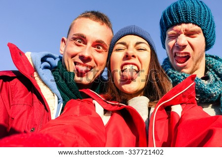 Group of friends having fun taking selfie with mobile - Smart students doing funny faces for holiday self photo - Young guys enjoying winter break using modern phone - Concept of youth and friendship