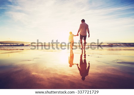 Father and Son Holding Hands Walking Together on the Beach at Sunset Royalty-Free Stock Photo #337721729