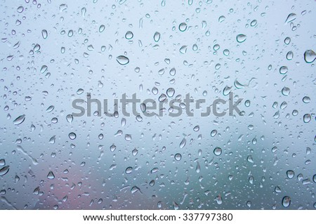 Blurred abstract background view of Rain drops on window surface with Boke Bowl, soft focus city view background