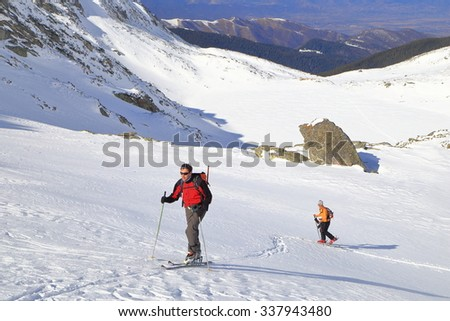 Snow covered valley and a couple of ski mountaineers ascending in sunny winter day #337943480