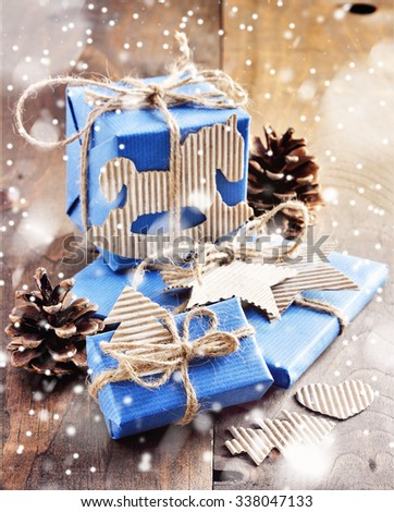 Christmas gift boxes, craft paper, handmade decoration, falling snow effect, toned image, selective focus #338047133