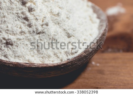 Wheat flour placed in a wooden spoon on the table Royalty-Free Stock Photo #338052398