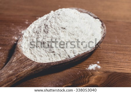 Wooden spoon filled with wheat flour on wooden table #338053040