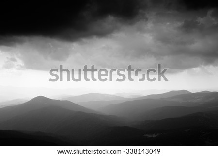 Mountain landscape. Mountain range in haze. Rays of light in lumen of mountains and clouds. Stormy weather. Panorama. Black and white photo