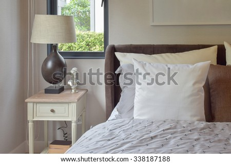 modern bedroom interior with white and brown pillow on bed and decorative table lamp #338187188