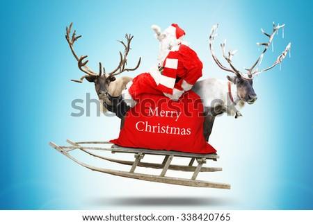 Santa Claus flies in a sleigh with reindeer #338420765