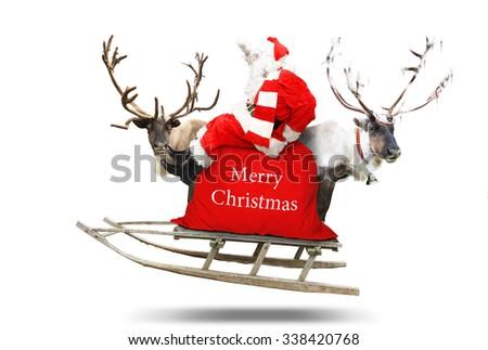 Santa Claus flies in a sleigh with reindeer #338420768