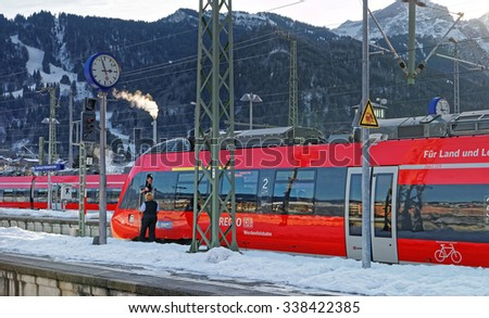 GARMISCH-PARTENKIRCHEN, GERMANY - JANUARY 6, 2015: Driver of a shiny red train awaiting departure at Garmisch-Partenkirchen train station on a sunny winter day. Bavaria. Germany #338422385