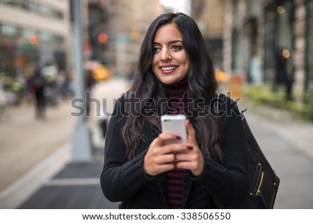 Indian woman in city texting cell phone #338506550