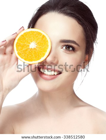 Great food for a healthy lifestyle. Beautiful young shirtless woman holding piece of orange in front of her eye while standing against white background and smile #338512580