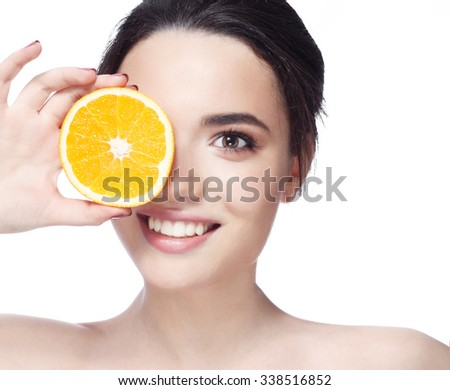 Great food for a healthy lifestyle. Beautiful young shirtless woman holding piece of orange in front of her eye while standing against white background and smile #338516852